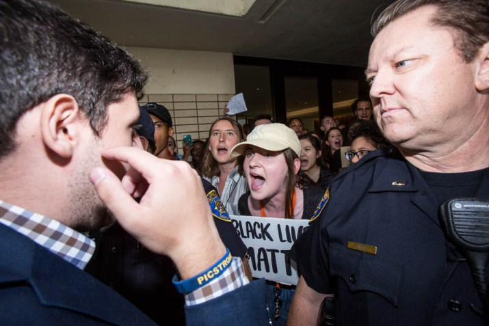 """A student in a blue suit stands across from a uniformed Campus Safety officer. Behind the officer are shouting students. One holds a sign reading """"Black Lives Matter."""