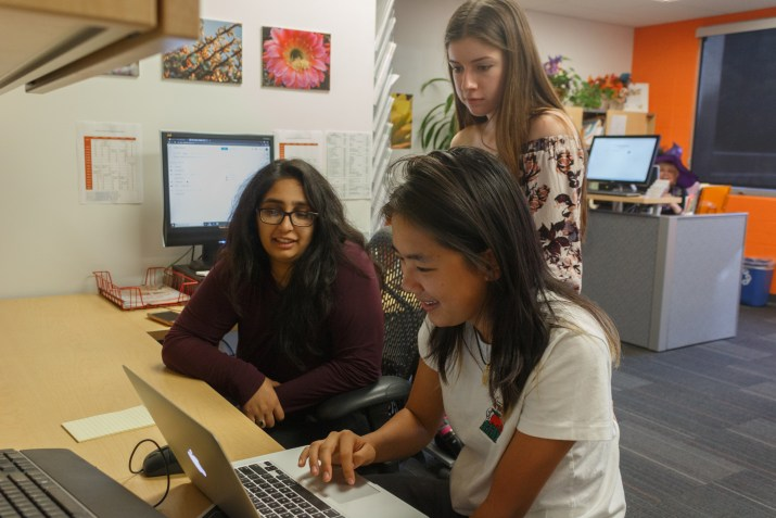 three smiling students look at a computer in the pitzer career office