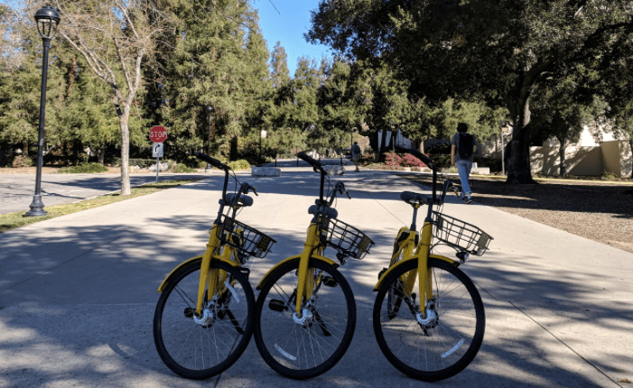 three yellow bikes lined up on a street