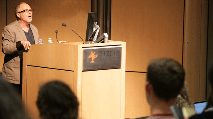 Artist, writer, and activist Gregory Sholette stands behind a podium as he delivers a lecture at Pitzer College.