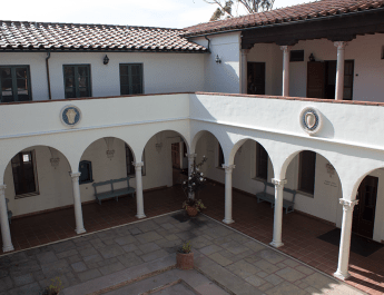 A courtyard surrounded by white archways on two sides.