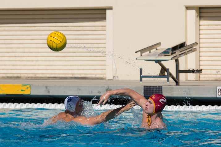 two men in a pool and a water polo ball in the air