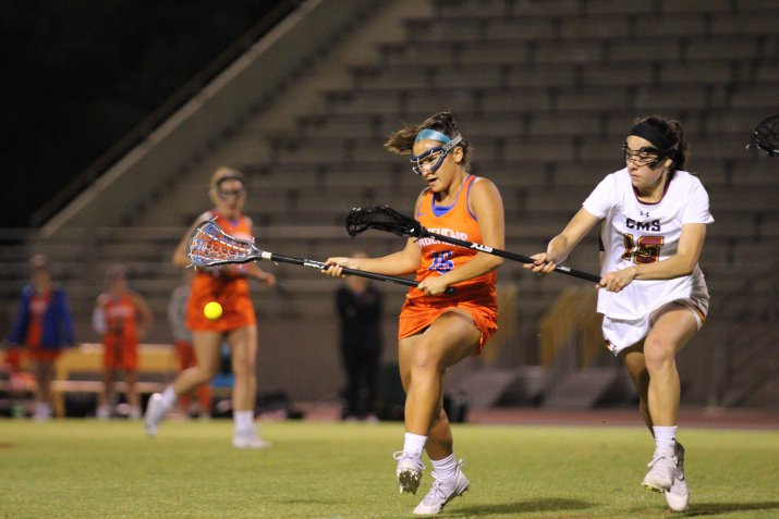 two female lacrosse players run parallel to each other