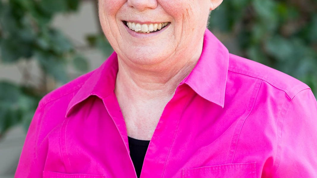 Harvey Mudd College Maria Klawe smiles in a bright pink shirt.