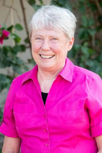 Harvey Mudd College Maria Klawe smiles in a bright pink shirt.