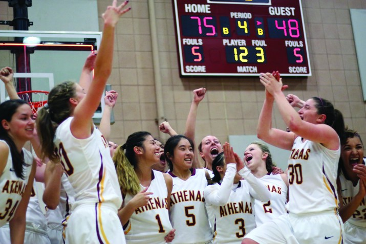 The Athenas basketball team cheers after winning a championship game