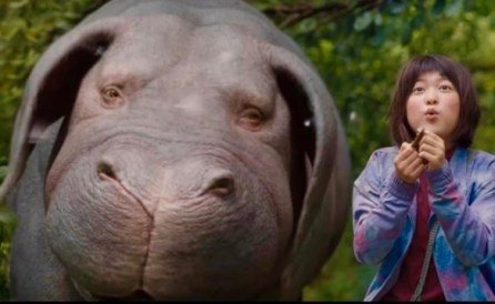 A giant hippo-looking animal and a girl with a bowl cut