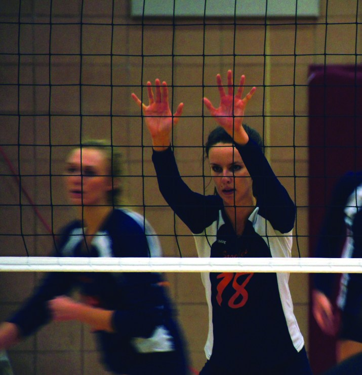 A female volleyball player puts her hands up