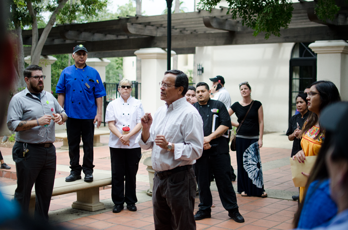 A man speaks to a crowd outside a dining hall