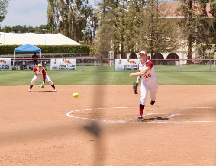 A female softball player pitches a ball