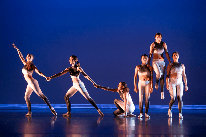 Six female students dance on a stage