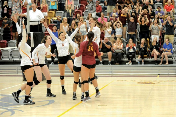 A group of volleyball players cheers on the court