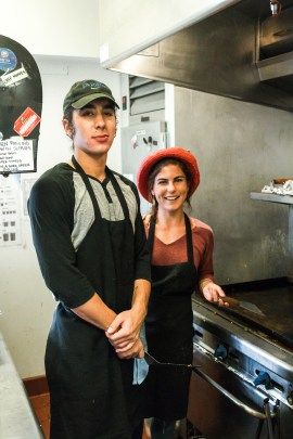 Jess Bird SC '19 and Eli Caplin PZ '18 in the Grove House. Caplin stands on the left and wears a black apron and green cap, while Bird is on the right and wears a black apron and red beret.
