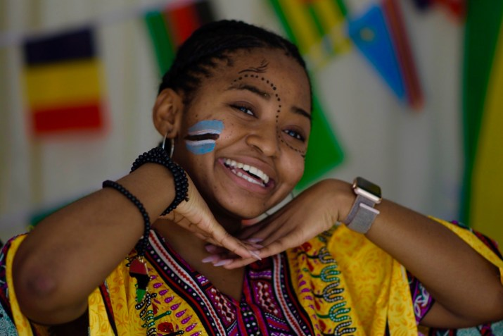 A girl with blue and black face paint smiles