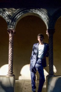 A young man stands in the shadows with an archway over him