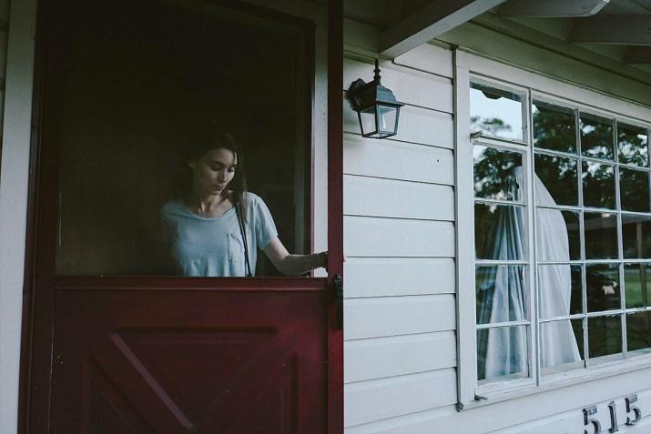 Girl walks through door of house to outside
