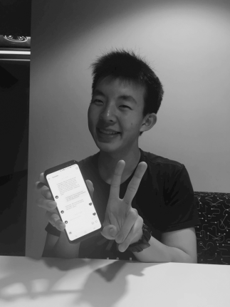 A young man holds up his phone and makes a peace sign with his left hand