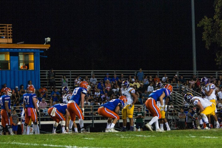 A group of football players stands on a field