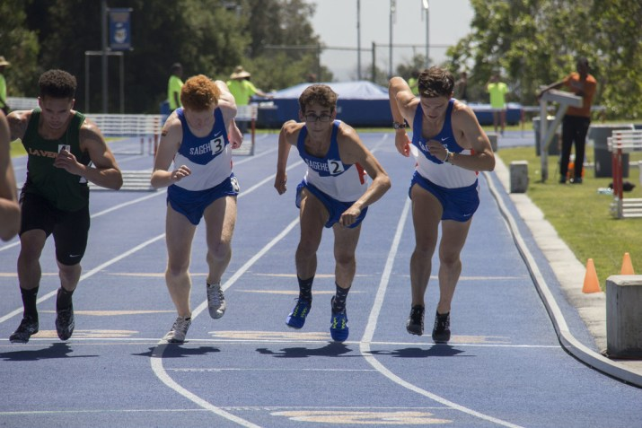 Four male track runners on a starting line