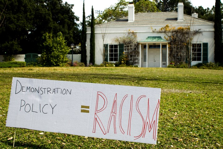 "A sign on a grass lawn that says ""demonstration policy = racism"""