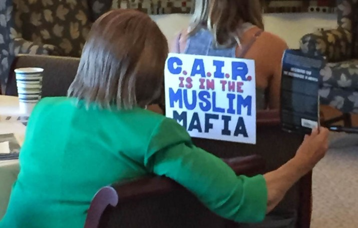 "Two women in a room with a sign that reads ""C.A.I.R. is in the Muslim mafia"""
