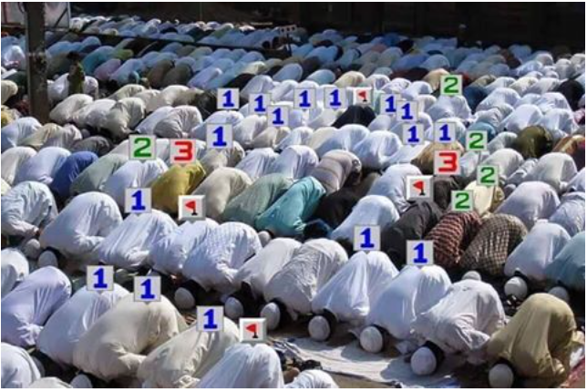 A group of Muslims praying with numbers on their backs