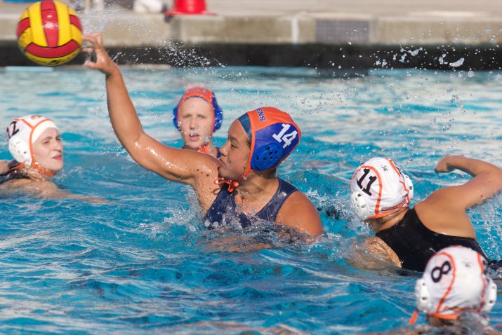 A waterpolo player throws the ball in the pool