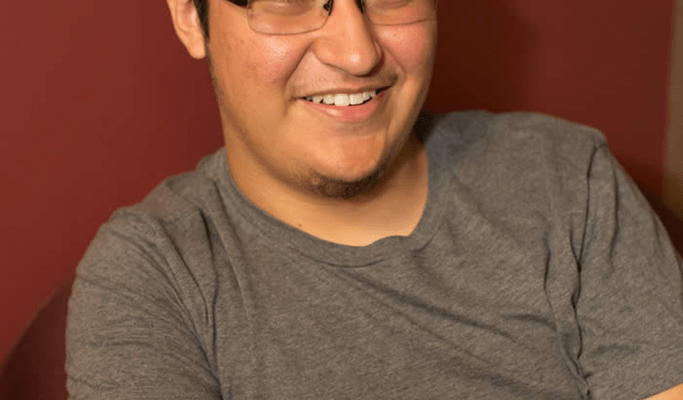 Willie Zuniga HM '17 wears a gray shirt and black glasses.