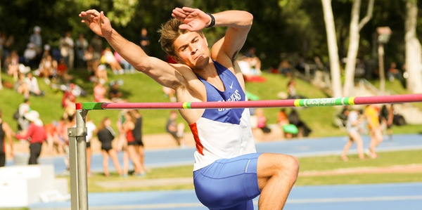 Cal Neikirk PO '19 in the midst of a high jump. He wears a blue, white and red uniform.
