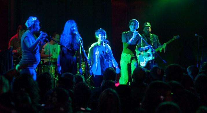 A photograph of Y La Bamba performing in a venue lit with blue and green light.
