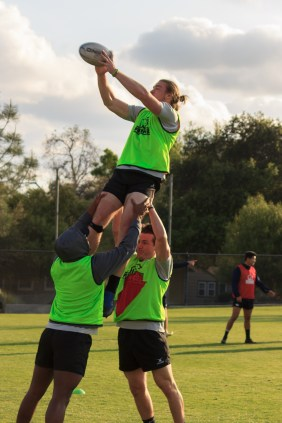 Two CMC rugby players lift one of their teammates into the air to catch a rugby ball during practice.