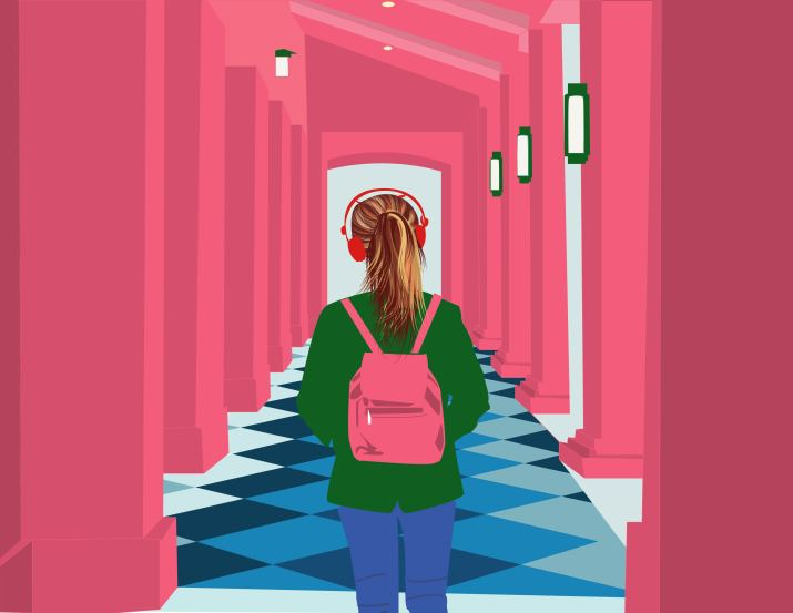 Female student with backpack and headphones walks through pink hallway