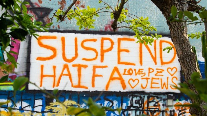 "A message reading ""Suspend Haifa. Love, PZ Jews"" is written on a wall in orange spray paint."