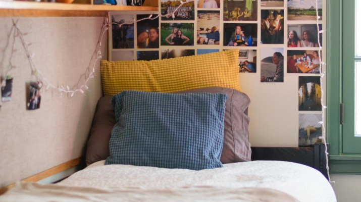 A dorm room with a bed and photos hanging on the wall behind the bed.