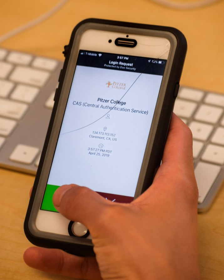 A student holds an iPhone in their hand. On the screen is a login page for a Pitzer College student account.