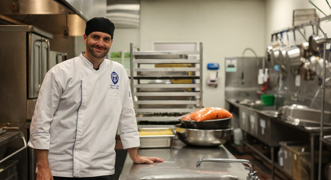 Chef Manager Travis Ellis stands next to his kitchen while preparing salmon in a pot