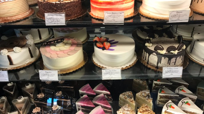 A picture showing three shelves of cakes. On the top shelf, from left to right, is a layered German chocolate cake, a layered lemon raspberry cake, and a layered horchata cake. On the second shelf, from left to right, is a layered Neapolitan cake, a layered berry tres leches cake, and a layered cookies n' cream cake. On the bottom shelf are a range of sliced cakes.