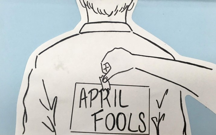 "A graphic of a man with a piece of paper saying ""April Fools"" being taped to his back, against a light blue background."