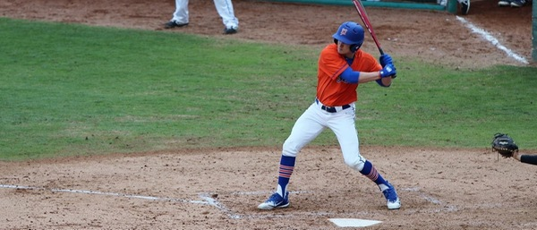 A player in an orange jersey, a blue undershirt, and white pants swings a red bat.