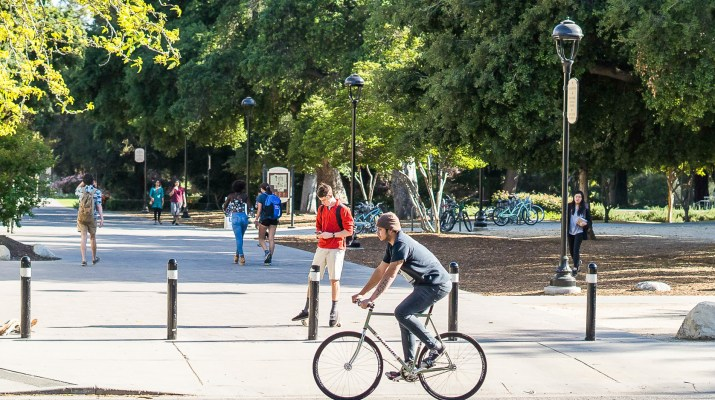 a person bicycling on college avenue, with bollards and people walking in the background