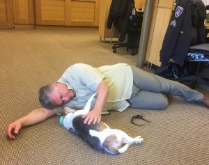 Stan Skipworth, a middle-aged caucasian man in a light green short sleeve button up and light olive cargo pants lies on the ground of the Claremont College's Campus Safety Department with Officer Bessie, a cute and portly old beagle.