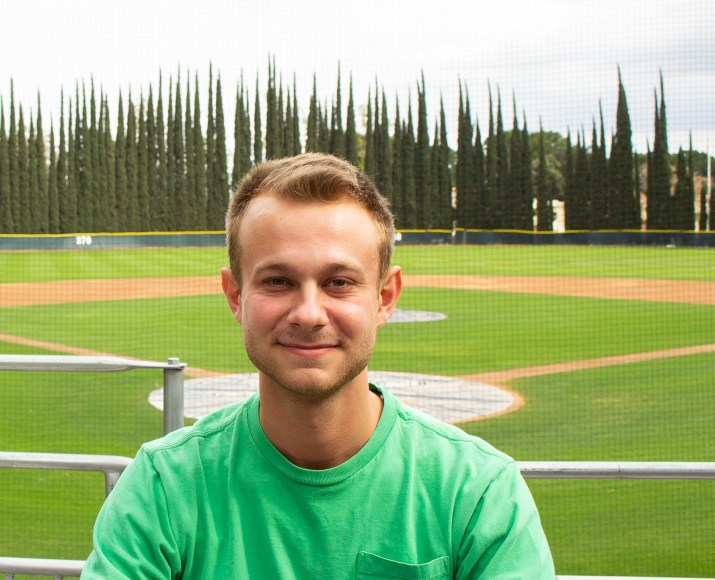 Gabe Fisher wears a green shirt and gives a wry smile as he sits in front of the CMS baseball diamond.