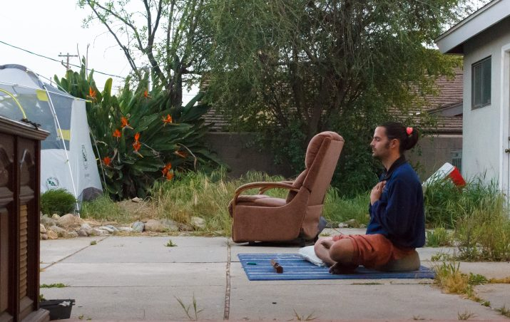 A man with a ponytail meditates outside
