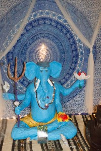 A blue elephant with hands sits cross-legged