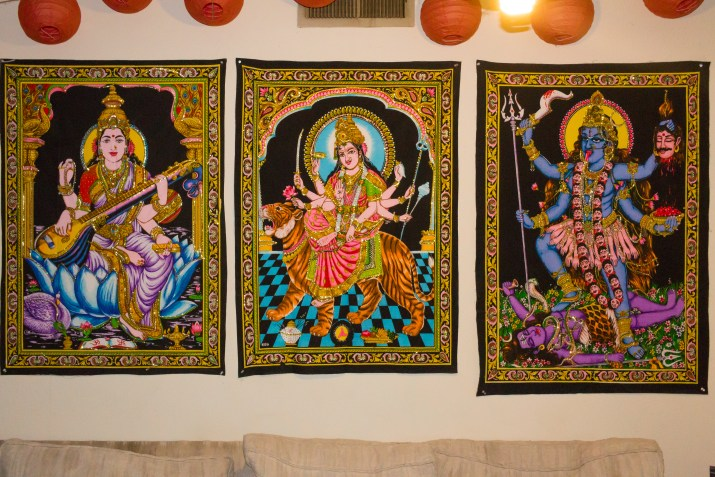 Three colorful tapestries featuring humanoid figures, representing Hindu gods, hang on a wall.