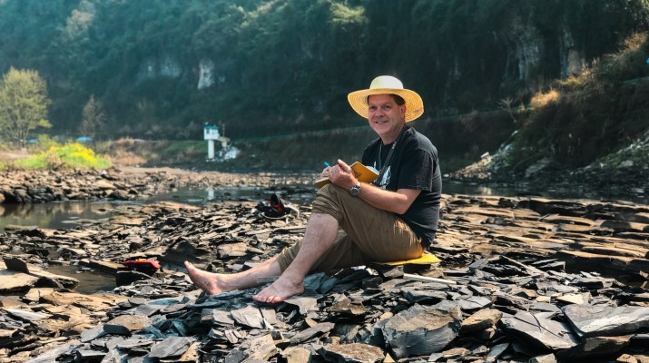 A man wearing a hat, Professor Robert Gaines, sits on rocks in a riverbed.