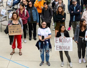 """A crowd of college students gather in a courtyard to rally for improved mental health resources. They hold signs saying """"My anxiety cannot wait 3 to 4 weeks!"""" and """"Enough is enough."""""""