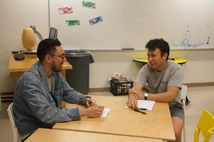 Gabriel Piscitello, a white male college student with dark brown hair wearing a light grey shirt and grey shorts sits across from Diego Vergara, a latino college student with a beard wearing glasses and a light blue denim jacket. They sit at a table in a classroom, writing notes and talking.