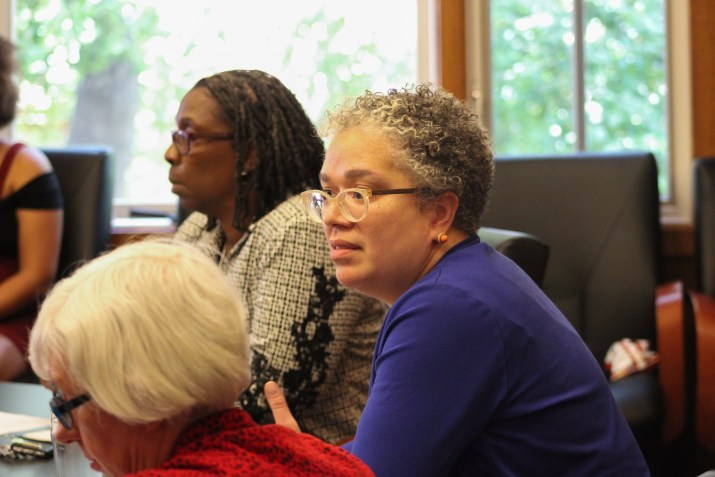 Pomona College President G. Gabrielle Starr, a middle-aged woman with curly grey hair, clear glasses, and an indigo shirt sits at a conference table during a sit-in.