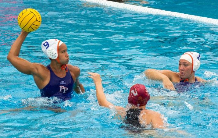 An player looks to score, holding the ball above her head, arm flexed.